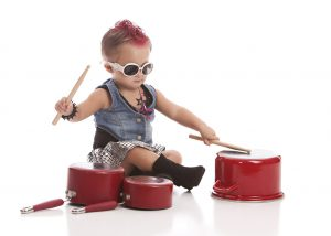 Adorable toddler dressed as a rock star with a hot pink Mohawk and drumming on some pots and pans. Isolated on white.