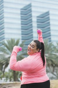 An Hispanic, overweight woman exercising outdoors, lifting handweights. She is looking over her shoulder at the camera, smiling. In the background is a modern office building and palm trees.